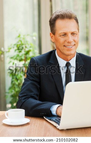 Working with pleasure. Cheerful mature man in formalwear working on laptop and smiling while sitting at the table outdoors - stock photo