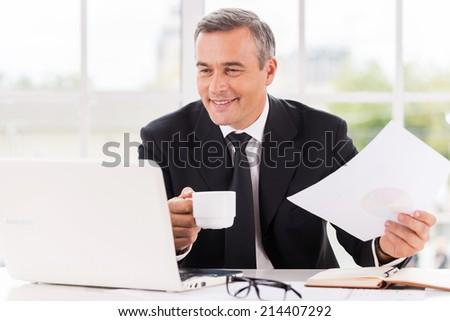 Working with pleasure. Happy mature man in formalwear working and drinking coffee while sitting at his working place - stock photo