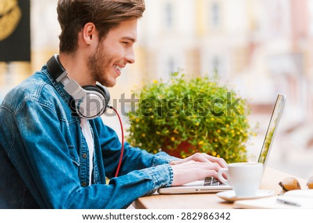 Working with pleasure. Side view of smiling young man working on laptop while sitting at sidewalk cafe - stock photo