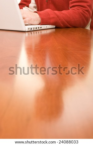 Working with white laptop in a red sweater on the wood table - stock photo