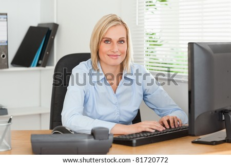 Working woman in front of a screen looks into camera in an office