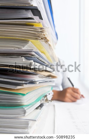 Workload concept with high pile of paperwork. Selective focus - stock photo