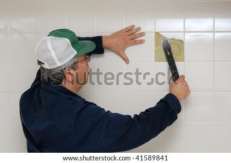 Workman breaking up bathroom tiles - stock photo
