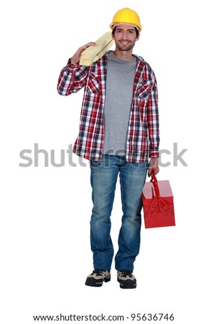 Workman carrying timber and a toolbox - stock photo