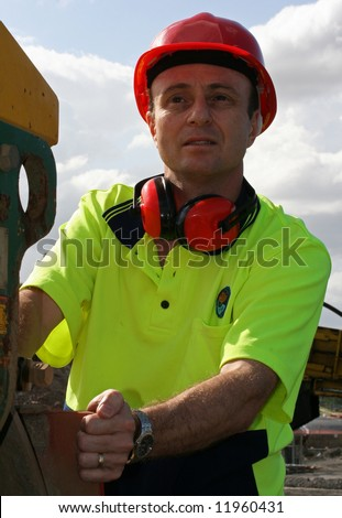 Workman dressed in reflective clothing, wearing a red helmet and air muffs about to climb on board the heavy plant machinery - stock photo