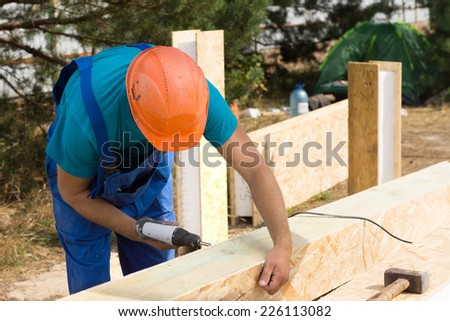 Workman drilling a hole in a wooden clad insulated beam on a new build construction site for a new house - stock photo
