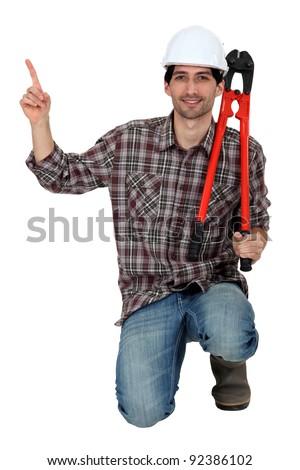 Workman kneeling, studio shot - stock photo
