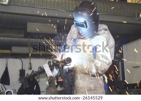 Workman / labourer welding a metal component - stock photo