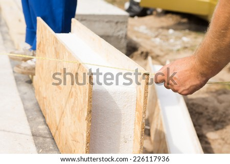 Workman measuring a prefab wooden wall panel with insulation on a construction site prior to installing it - stock photo