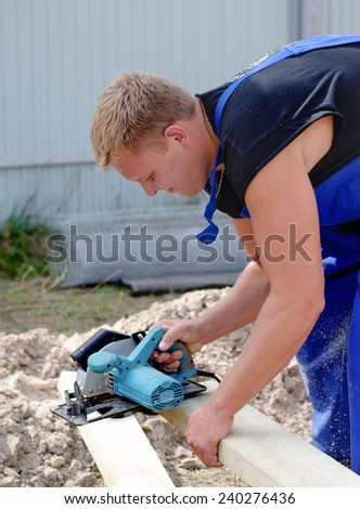 Workman or carpenter on a building site cutting a wooden beam to length with an electric power tool