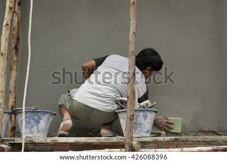 Workman plaster at construction site,Plaster concrete worker at wall of house construction,Building construction site - stock photo