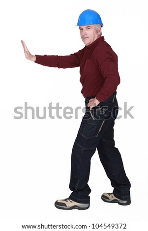 Workman pushing an invisible wall - stock photo