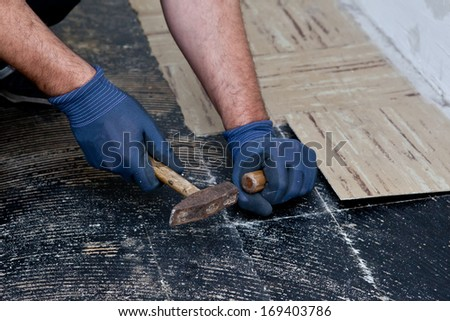 Workman removing old floor tiles using a hammer and chisel during building renovations so that he can install new flooring, close up view of his gloved hands - stock photo
