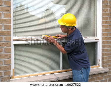 Workman repairing a large picture window - stock photo