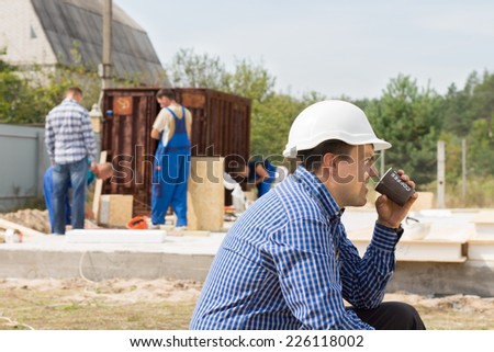 Workman sitting relaxing drinking coffee on a building site while his colleagues continue working, side view in a hardhat - stock photo