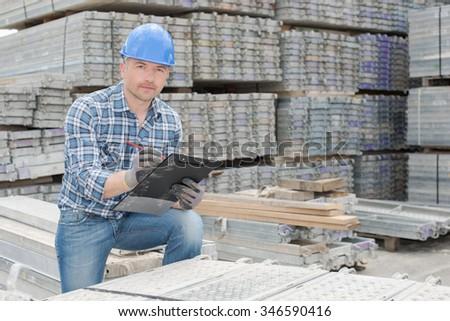 Workman stood with cast concrete slabs - stock photo