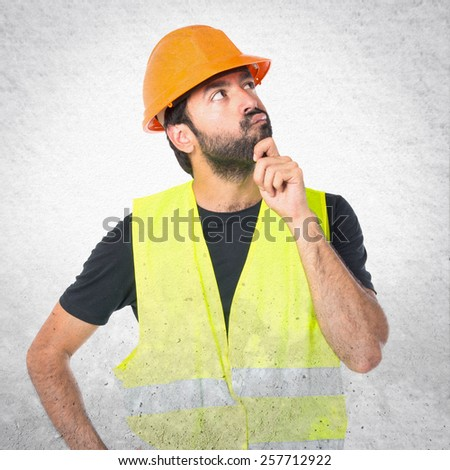 Workman thinking over textured background - stock photo