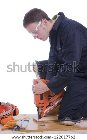 workman using electric nail gun on wood with white background - stock photo