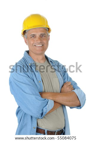 Workman wearing a yellow hard hat and smiling at the camera with his arms crossed. Isolated over white in vertical format. - stock photo