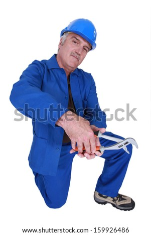 Workman with an adjustable spanner - stock photo