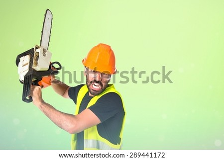Workman with chainsaw over shiny background - stock photo