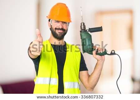 workman with drill on unfocused background