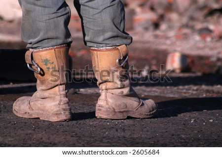 Workmans boots, demolition worker taking a break, looking over his work - stock photo
