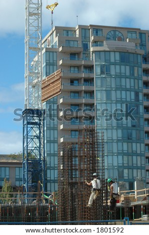 Workmen climbing rebar grid at construction site - stock photo