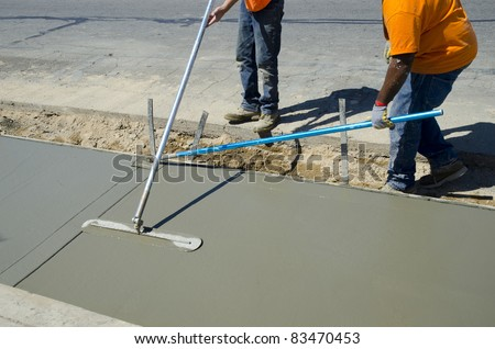 Workmen finish and smooth concrete surface on new sidewalk - stock photo