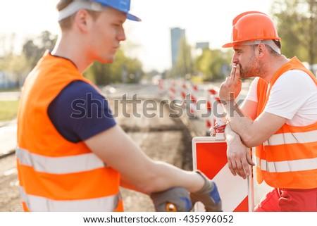 Workmen having a break and smoking a cigarette - stock photo