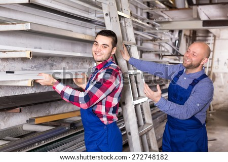 Workmen in a warehouse are taking an aluminum window frame from a rack - stock photo