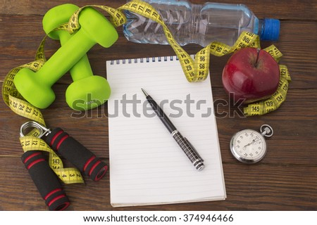 Workout and fitness dieting copy space diary. Healthy lifestyle concept. Apple, dumbbell, water, expander hand, stopwatch and measuring tape on rustic wooden table. - stock photo