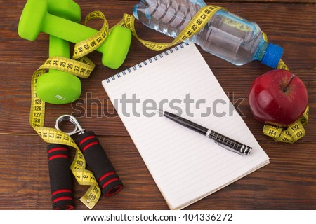 Workout and fitness dieting copy space diary. Healthy lifestyle concept. Apple, dumbbell, water, expander hand and measuring tape on rustic wooden table. - stock photo