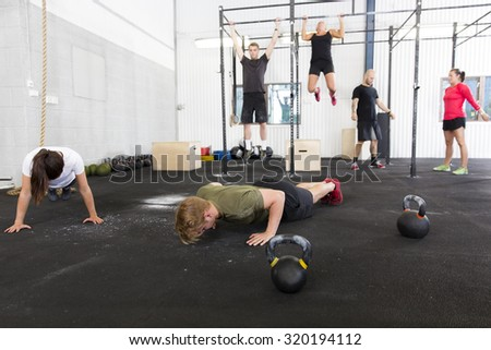 Workout group does exercises at fitness gym - stock photo