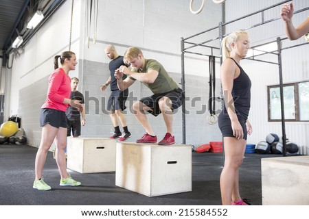 Workout group trains box jumps - stock photo