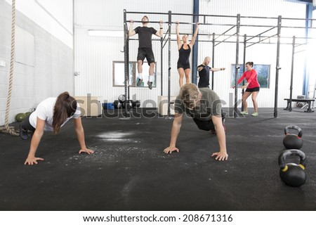Workout group trains exercises at fitness gym - stock photo