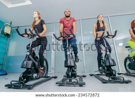 Workout in the gym. Three sports friends pedaling and looks in front of a stationary bicycles at the gym while their friends are athletes pedaled on bicycles in the background - stock photo