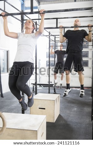 Workout team trains pullups at fitness gym - stock photo