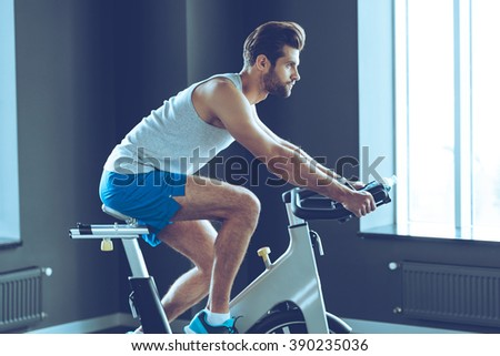 Workout with strength. Side view of young handsome man in sportswear cycling at gym - stock photo