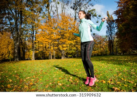 Workout - young woman jumping with skipping rope - stock photo