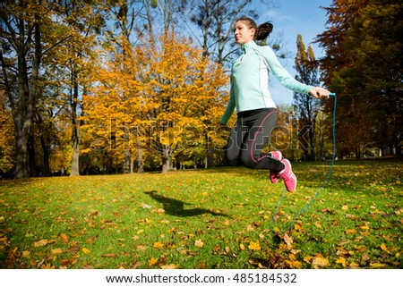 Workout - young woman jumping with skipping rope