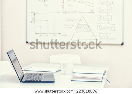 Workplace at the office with laptop computer and whiteboard. Training classroom. - stock photo