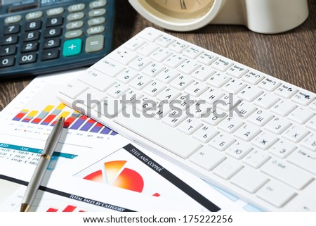 workplace businessman with keyboard, papers, calculator and clock - stock photo
