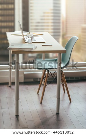Workplace freelance designer, Modern desktop in loft, beautiful views of the city centre, desktop with modern laptop, flowers on the wooden desk. Desktop with a view of downtown, Sunrise, Shallow DOF. - stock photo