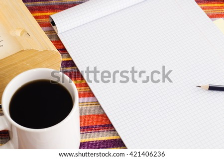 Workplace in vintage style: open blank page notebook,  pencil,  book and  cup of coffee, top view. - stock photo
