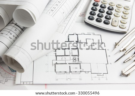 Workplace of architect - Architectural project, blueprints and calculator, divider compass on plans. Engineering tools view from the top. Construction background.