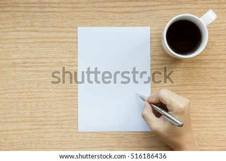 Workplace of wooden desk with a hand hold a pen for writing on empty white paper with a cup of coffee