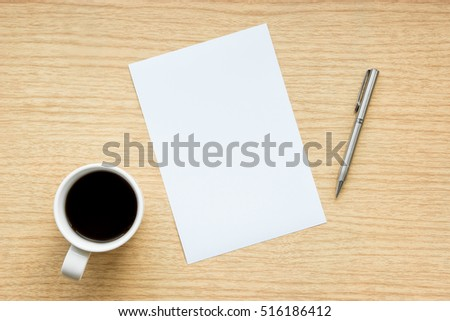 Workplace of wooden desk with a pen and empty white paper with a cup of coffee