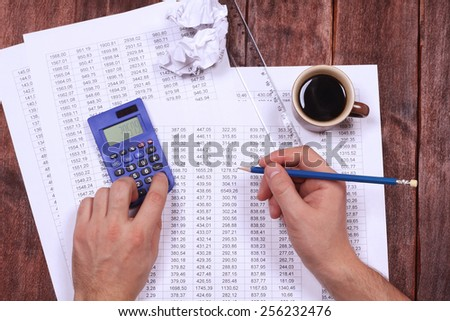 Workplace office worker. Working hard. A cup of coffee, crumpled paper, a pencil, a calculator. Office desk. Accountant job. Accounting report, verification of numbers, counting on a calculator. - stock photo