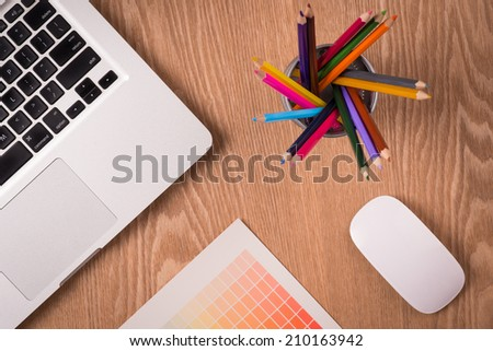 Workplace with colored pencils, laptop, palette on wooden table. Above view - stock photo